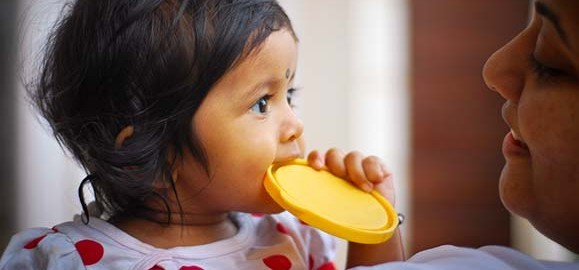 Child biting on lid