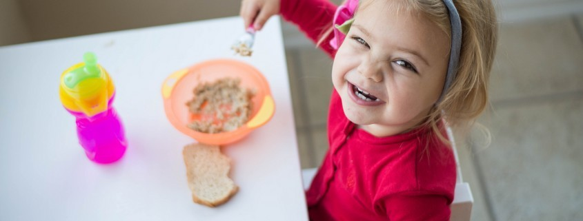 Smiling young toddler eating breakfast