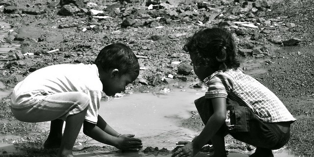 Two young children playing in the creek