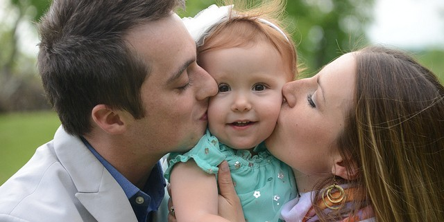 Man and Woman hugging their young daughter