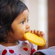 Child biting on lid