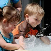Two young kids splashing in a play pool