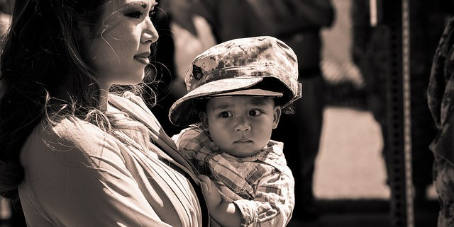 Mother holding her child wearing defence force outfit