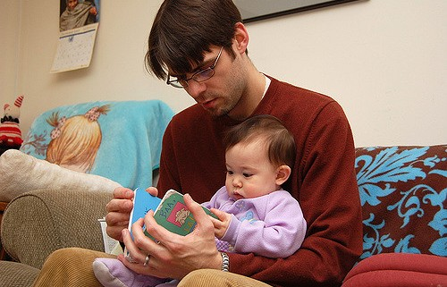 Dad reading a book to his young baby sitting on his lap