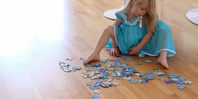 Child sitting on the floor, intently doing puzzle